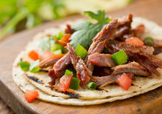 Pork Taco. A delicious pulled pork taco with tomato, jalapeno pepper, green onion, and cilantro on a grilled corn tortilla Stock Images