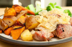 Pork tenderloin. Grilled pork tenderloin medallions with apple and sweet onion sauce served with yams and potatoes and greens Royalty Free Stock Image
