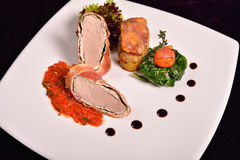 Pork tenderloin in bacon wrap with tomato sauce flavored with ro Stock Photography