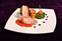 Pork tenderloin in bacon wrap with tomato sauce flavored with ro Royalty Free Stock Photos