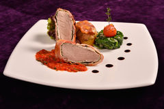 Pork tenderloin in bacon wrap with tomato sauce flavored with rosemary Stock Photo
