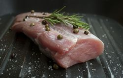 Pork tenderloin with green pepper, rosemary and sea salt in grill pan. Tenderloin is soft juicy part of pork which some people prepare on circular pieces or stock photos