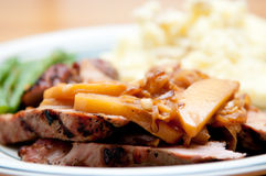 Pork tenderloin medallions with apple. Grilled pork tenderloin medallions with apple and sweet onion sauce served with mashed potatoes and green string beans Stock Photo