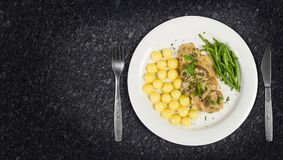 Pork tenderloin with potatoes and wild mushroom sauce and green beans on white plate royalty free stock photo