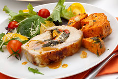 Pork Tenderloin Roulade and Salad. Feta-, spinach-, and bell pepper - stuffed pork tenderloin roulade garnished with sweet potato and green salad Royalty Free Stock Photos