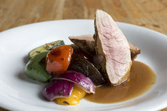 Pork tenderloin steak with grilled vegetables and sauce. Stock Images