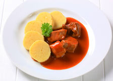 Pork in tomato sauce with potato dumplings Stock Image