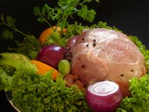Pork and vegetables. Fresh pork meat garnished with lettuce, purple onion, orange slice, apple and parsley Stock Photography