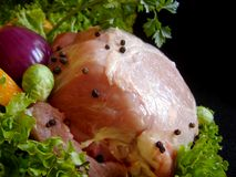 Pork and vegetables. Fresh pork meat garnished with lettuce, purple onion, orange slice, apple and parsley stock photos