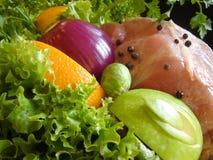 Pork and vegetables. Fresh pork meat garnished with lettuce, purple onion, orange slice, apple and parsley Stock Image
