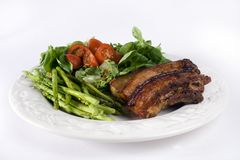 Pork and vegetables. A plate of food that consist of asparagus, salad with tomato, and pork isolated on a white background Stock Photography