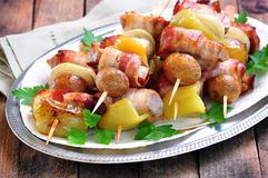 Pork wrapped in bacon on skewers grilled with onions, mushrooms and peppers. Stock Photo