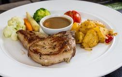 Porkchop served on white dish Stock Photos