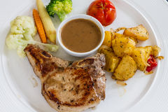 Porkchop served on white dish Royalty Free Stock Images