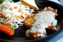 Porkchop and vegetables. Salad on black dish stock photo