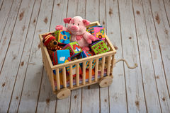 Porky pink and teddy bear are playing in the cart Stock Image