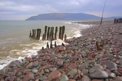 Waves on cobble beach. Wooden piles on the cobble beach at Porlock Weir, Somerset, England Stock Photo