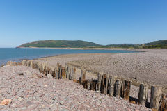 Porlock Weir beach Somerset uk in summer. With blue sky and line of posts Stock Images