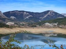 Porma Reservoir in summer, with little water. Reflections on the water of the Porma Reservoir, Boñar Spain, with very low water level. It is summer, the Royalty Free Stock Image