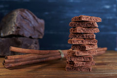 Porous chocolate and cinnamon on a wooden background Stock Images