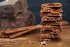 Porous chocolate and cinnamon on a wooden background Royalty Free Stock Photos