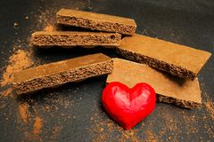 Porous chocolate and red heart on a black background royalty free stock photos