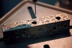 Porous metal brick with holes. Royalty Free Stock Photos