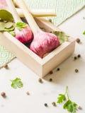 Porpora dell'aglio con prezzemolo in scatola di legno su un fondo di pietra bianco Immagine Stock
