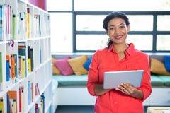 Porrait van leraar die digitale tablet in schoolbibliotheek gebruiken Stock Foto's
