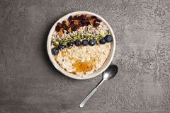 Porridg with blueberries and dried fruit. Porridge with blueberries and dried fruit, nuts, seeds and honey in a pottery bowl with a teaspoon and split colour royalty free stock images