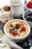 Porridge with addition fresh berry fruits, almond flakes, sesame seeds, lemon zest and honey Royalty Free Stock Photos