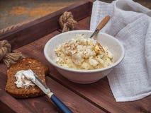 Porridge appena preparato del riso del latte, in un piatto profondo un cucchiaio con una maniglia di legno, pani tostati con form fotografie stock