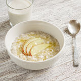 Porridge with apple and honey in a white bowl and a glass of  natural yoghurt Royalty Free Stock Images