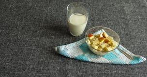 Porridge with apple slices, a glass of milk. stock photography