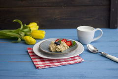 Porridge with berries, fresh strawberries and blueberries. Strewing with powdered sugar Royalty Free Stock Image