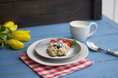 Porridge with berries, fresh strawberries and blueberries. Strewing with powdered sugar Royalty Free Stock Photos