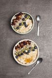 Porridge with blueberries and dried fruit. Two bowls of porridge with blueberries and dried fruit, nuts, seeds and honey in a pottery bowl with a teaspoon and stock images
