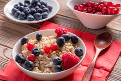 Porridge with blueberries and raspberries and grain bread on wooden background. Healthy vegan breakfast. Close up view of porridge with blueberries and royalty free stock photos