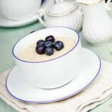 Porridge in breakfast cup on a blue wooden table Royalty Free Stock Images