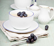 Porridge in breakfast cup on a blue wooden table Royalty Free Stock Photos