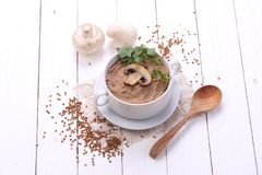 Porridge with champignons. Porridge with mushrooms in a ceramic bowl, fresh onions and sour cream on wooden white background Royalty Free Stock Images