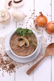Porridge with champignons. Porridge with mushrooms in a ceramic bowl, fresh onions and sour cream on wooden white background Royalty Free Stock Photography