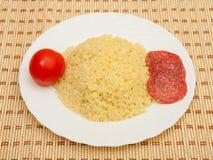 Porridge con salame ed il pomodoro Fotografia Stock