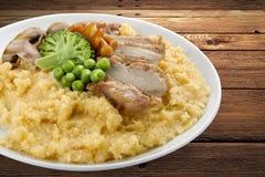 Porridge del grano con carne di maiale e le verdure fotografia stock