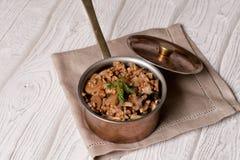 Porridge del grano saraceno con i funghi nella pentola di rame immagini stock libere da diritti