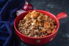 Porridge del grano saraceno con le salsiccie e le cipolle fritte in una pentola rossa su un fondo scuro, spazio della copia fotografia stock
