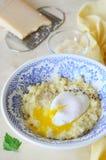 Porridge del miglio con l'uovo affogato ed il formaggio grattugiato immagine stock