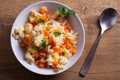 Porridge del riso con la zucca, le mele e l'uva passa in ciotola bianca Piatto vegetariano di dieta di riso e della zucca Aliment fotografia stock