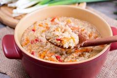 Porridge dell'orzo su un cucchiaio di legno immagini stock