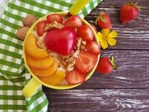 Porridge della farina d'avena, albicocca, fragola, cuore della prima colazione su un fondo di legno immagini stock libere da diritti